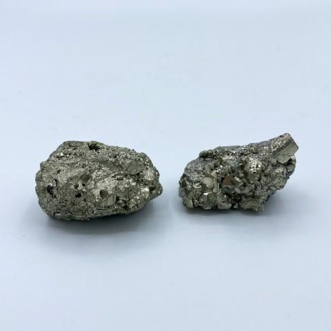 2 stukjes pyriet op een witte achtergrond