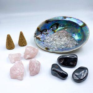 Schelp met bergkristal erin, daar voor liggen 3 stenen hematiet, 4 stukjes rozenkwarts en 2 kegels palo santo