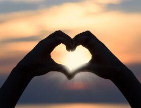 2 handen tegen elkaar die een hartje vormen tijdens zonsondergang.