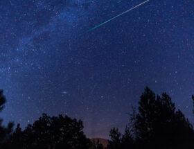 Afbeelding van de nacht met vallende sterren en bomen aan de onderkant